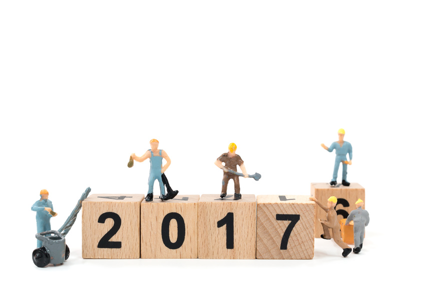 Miniature worker team building wooden block number 2017 on white background