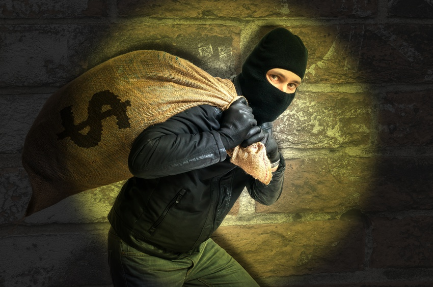 Burglar is carying full bag of money and is catched with flash light at night.