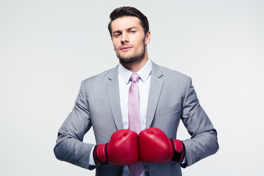 Handsome businessman standing with boxing gloves over gray background. Looking at camera
