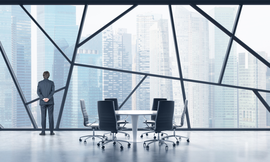 Rear view of a full length man in a formal suit who is looking out the window in a modern panoramic meeting room in Singapore. The concept of highly professional financial or legal services.